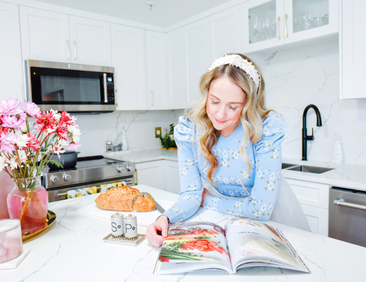 Halifax blogger poses reading a cook book and fresh bread in her newly renovated kitchen