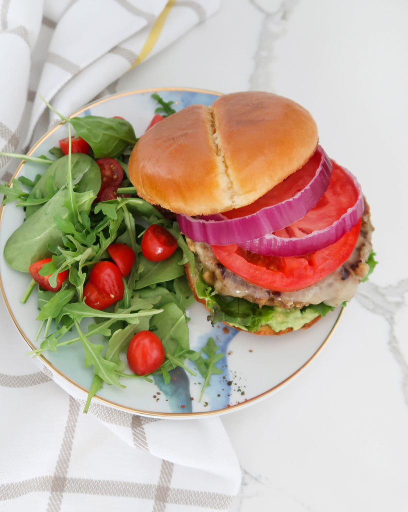 Turkey burger with tomato and onion served with a side salad