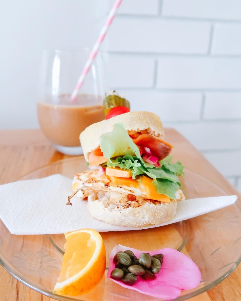 Breakfast sandwich with egg, chees, lettuce, and salmon feautred with ice coffee and cappers with an orange slice