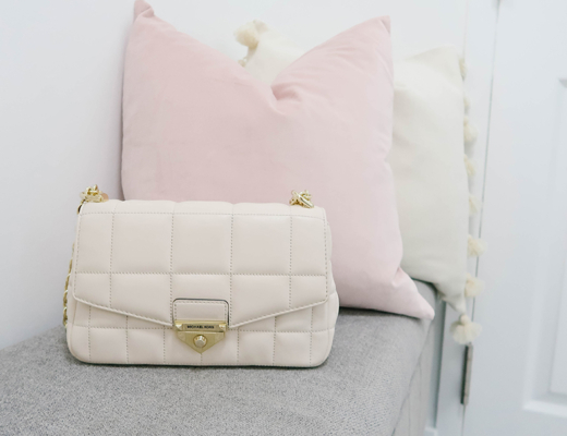 Michael Kors Soho Purse sits on a gray bench with pink throw pillows