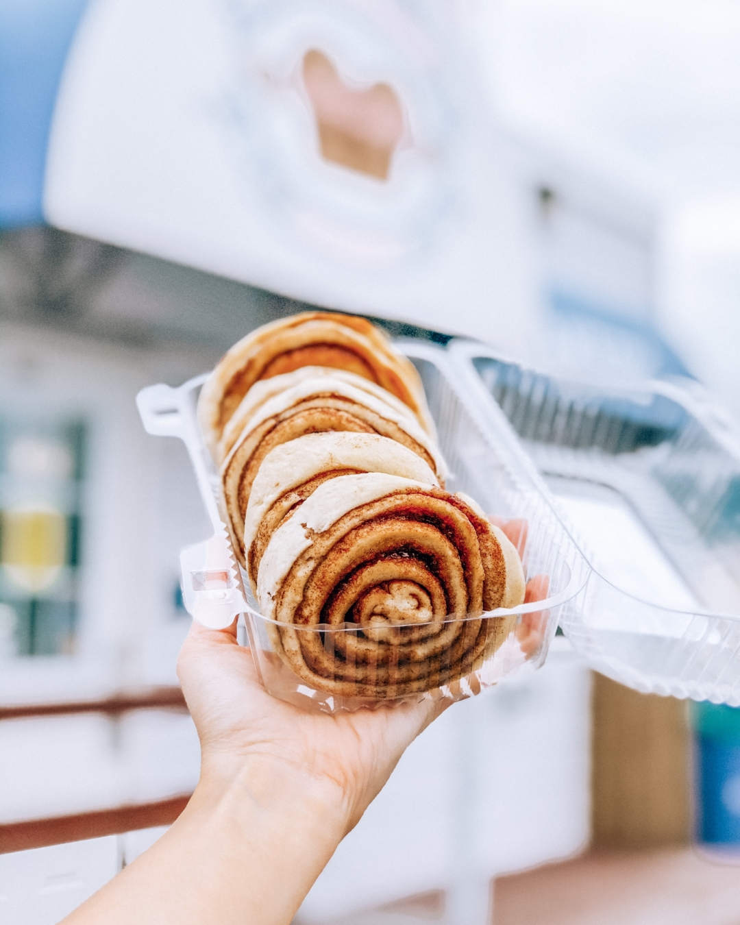 Fresh cinnamon rolls in a plastic container held by Halifax Blogger