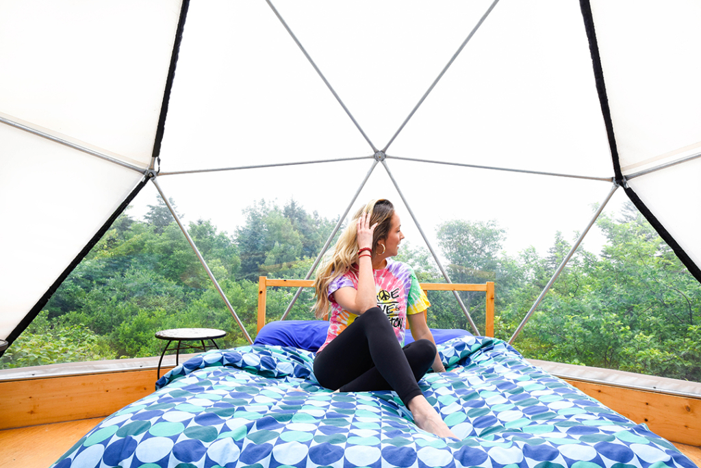 Blogger poses on a bed in a glamping dome wearing tie dye shirt