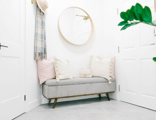 A gray bench sits with cozy pillows and round mirror above and hook to the side with a hat and scaf
