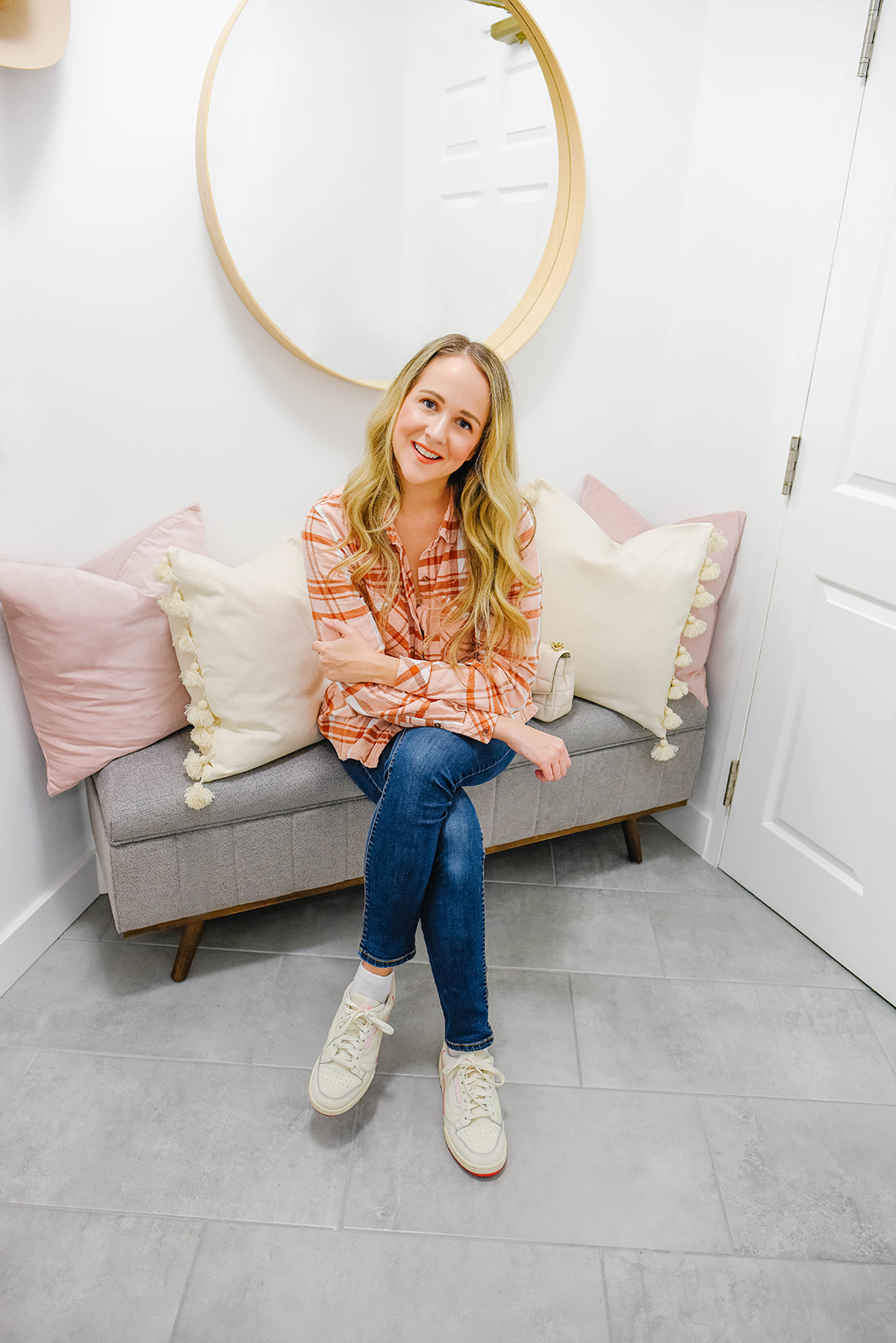 Blogger Kayla Short posed on gray bench with cozy pillows and a round mirror behind